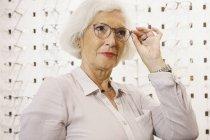 Donna anziana con gli occhiali al negozio — Foto stock