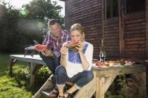 Щасливі Літня пара насолоджуючись кавун сидячи за межами фермерському будинку на сонячний день — стокове фото