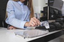 Section milieu de la vendeuse utilisant la carte de crédit au comptoir de caisse en magasin — Photo de stock