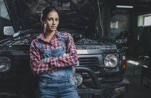 Ritratto di meccanico donna fiduciosa con braccia incrociate appoggiate all'auto in officina — Foto stock