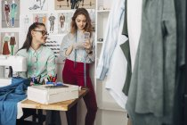 Happy designer looking at female trainee holding container in design studio — Stock Photo