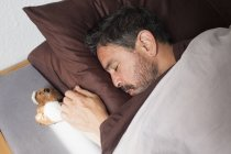 Mature man sleeping with small teddy bear on bed at home — Stock Photo