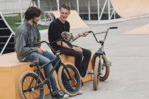 Alegres amigos descansando en el asiento con las bicicletas en el parque de Skate - foto de stock