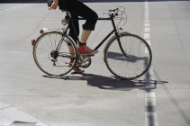 Bassa sezione di giovane donna in bicicletta — Foto stock