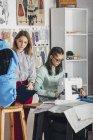 Asistente de pie y diseñadora femenina trabajando en la máquina de coser en el estudio - foto de stock