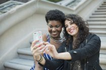 Happy woman taking selfie with young female friend against steps — Stock Photo