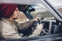 Side view of man wearing knit hat riding sport utility vehicle — Stock Photo