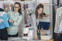 Assistant and female fashion designer working in studio — Stock Photo