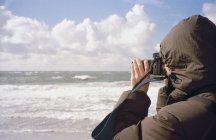 Vista laterale della persona che scatta foto sulla spiaggia — Foto stock