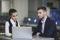 Giovane uomo d'affari e donna di affari che utilizza computer portatile all'aeroporto — Foto stock