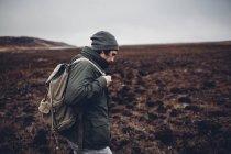 Randonneur portant sac à dos tout en marchant sur un paysage aride, Blagoveschensk, Amour, Russie — Photo de stock