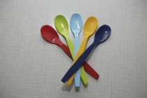 Colorful baby plastic spoons on table — Stock Photo