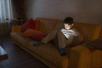 Хлопчик, використовуючи цифровий планшет, сидячи на дивані у себе вдома — стокове фото