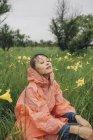 Jovem relaxante em meio a plantas de flores amarelas durante a estação chuvosa — Fotografia de Stock