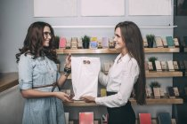 Young saleswoman handing over plastic bag to female customer in store — Stock Photo