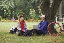 Homem com laptop conversando com amigo enquanto sentado na grama no parque — Fotografia de Stock