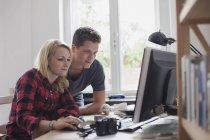 Молода пара, використовуючи комп'ютер проти вікна будинку — стокове фото