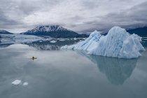 Persona canoa in laguna da iceberg contro cielo nuvoloso, Lago George, Palmer, Alaska, Stati Uniti d'America — Foto stock
