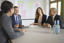Smiling business people having meeting at board room — Stock Photo