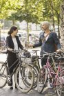 Business colleagues talking while standing with bicycles in parking lot — Stock Photo