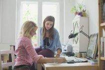 Giovani universitari femminili studiando a casa — Foto stock