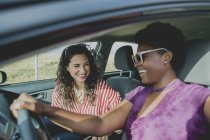Happy woman looking at young friend driving car — Stock Photo
