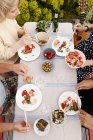 Amis mâles et femelles en train de déjeuner à table en plein air — Photo de stock