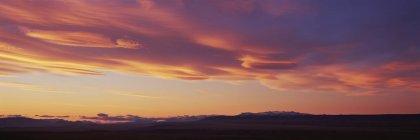 Vue panoramique du paysage avec un ciel orange pendant le coucher du soleil — Photo de stock