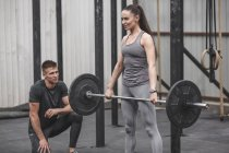 Male instructor looking at young woman crossfit training at gym — Stock Photo