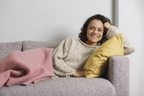 Portrait of happy woman relaxing on sofa at home — Stock Photo