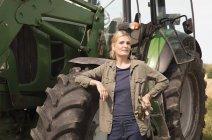 Портрет зрілої жінки стоять біля трактора ферми — стокове фото