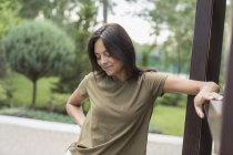 Улыбающаяся женщина смотрит вниз, стоя у перила — стоковое фото
