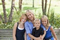 Mamma e bambini su una panchina — Foto stock