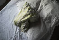 Low angle view of crumpled sheet and pillow on white bed — Stock Photo