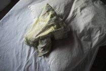 Visão de baixo ângulo de folha enrugada e travesseiro na cama branca — Fotografia de Stock