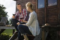 Mature couple talking and having wine while resting outside farmhouse — Stock Photo