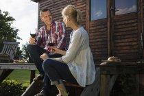Зрелая пара разговаривает и выпивает вино во время отдыха на ферме — стоковое фото