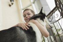 Низький кут портрет хлопчик всеосяжне собаку за для східців вдома — стокове фото