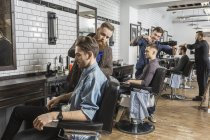 Hairdressers cutting male customer's hair in salon — Stock Photo