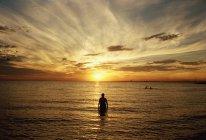Silhouette de l'homme debout en mer au coucher du soleil — Photo de stock
