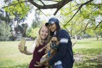 Усміхаючись молодих жінок, що приймають selfie з собакою у парку — стокове фото