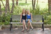 Dos chicas piernas cruzadas en un banco - foto de stock