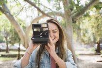 Mujer joven feliz con cámara instantánea en el Parque - foto de stock