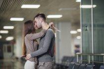 Seitenansicht des romantischen junge Paar küssen am Flughafen — Stockfoto