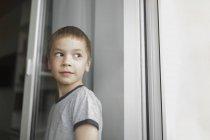 Мальчик смотрит в сторону, стоя у стены — стоковое фото
