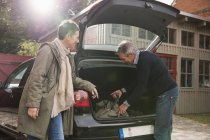 Woman watching man packing luggage in trunk — Stock Photo