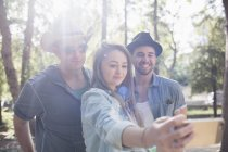 Young woman taking selfie with male friends with smartphone in park during sunny day — Stock Photo