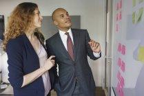 Gli uomini d'affari discutono su appunti adesivi in ufficio creativo — Foto stock