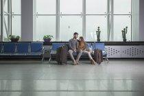 Молодая пара с багажом, сидя на стульях в аэропорту — стоковое фото