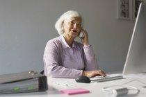 Lächelnde Geschäftsfrau, die mit dem Handy telefoniert, während sie im Büro am Computer arbeitet — Stockfoto